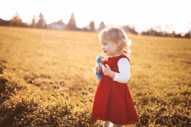Blondes Mädchen mit Kuscheltier auf Feld