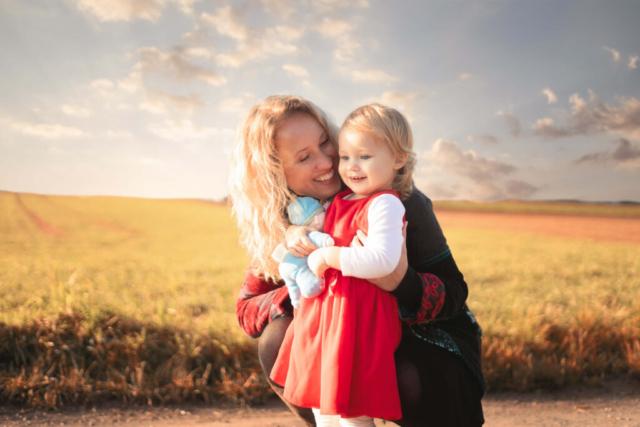 Mutter mit Kind im Arm vor einem Feld